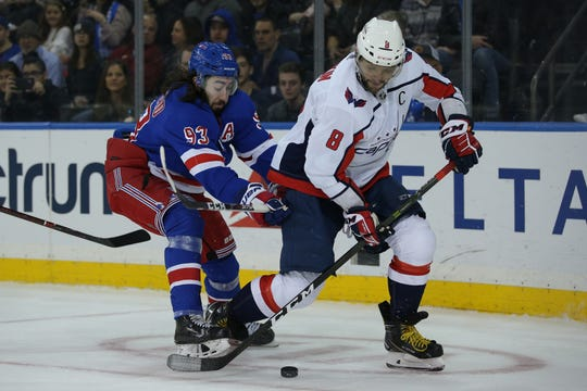 Mar 5, 2020; New York, New York, USA; Washington Capitals left wing Alex Ovechkin (8) plays the puck against New York Rangers center Mika Zibanejad (93) during the first period at Madison Square Garden. Mandatory Credit: Brad Penner-USA TODAY Sports