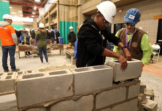 Khaliq Ortiz, left, a junior at Chester Academy, learns how to lay block from John Derham of Local 1 Masonry out of Newburgh at the 21st Construction Career Day hosted by the Construction Industry Council of Westchester and Hudson Valley Inc. March 6, 2020 at Rockland Community College in Suffern.