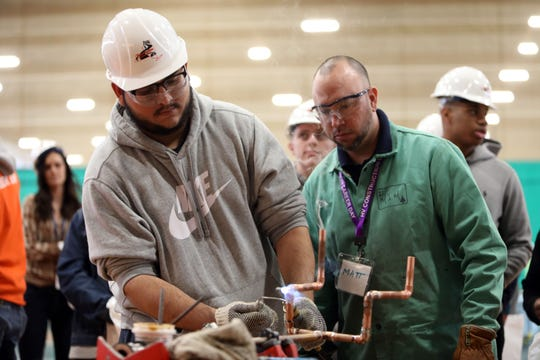 Jacob Rodriguez of Valley Central High School tries soddering under the guidance of Matt Mangone from Local 21 Plumbers & Steamfitters at the 21st Construction Career Day hosted by the Construction Industry Council of Westchester and Hudson Valley Inc. March 6, 2020 at Rockland Community College in Suffern.