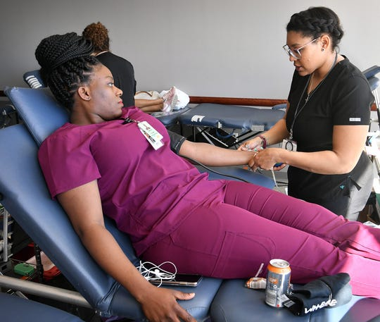 Midwestern State University nursing student Adetute Balogun, left, prepares to donate blood as Paige James of the Texas Blood Institute gets ready during the 20th annual Community Health Fair Friday.