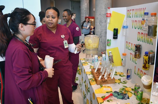 Nurcan Ince, right, listens as Selamawit Kidane describes the amount of sugar in various drinks compared to water at the 20th Annual Community Health Fair at Midwestern State University Friday morning.