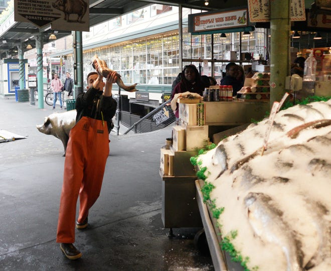 Fishmonger Nic Grimmer catches a whole salmon at the Pike Place Fish Market in Seattle on Thursday, March 5, 2020, during an outbreak of coronavirus that prompted local authorities to recommend that people temporarily work from home and avoid large gatherings.