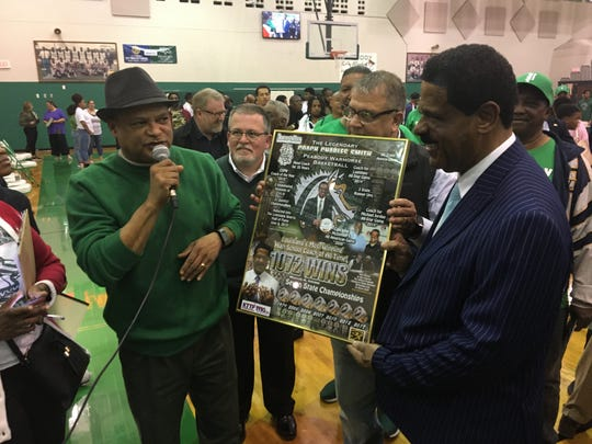 KTTP radio host Tony Brown (left) presents a commemorative poster to Peabody coach Charles Smith after winning his 1,072nd game, the most of any Louisiana basketball head coach.