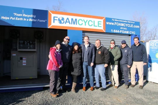 Middletown officials stand by the township's new polystyrene processing machine in December.