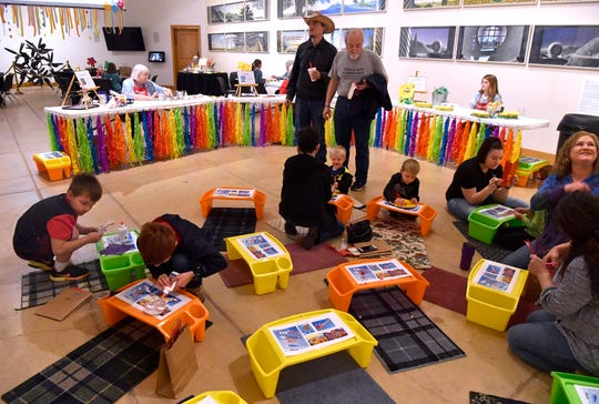 Children spread out to make their kites, using plastic desks, colors and materials such as plastic plates, Popsicle sticks and bunting.
