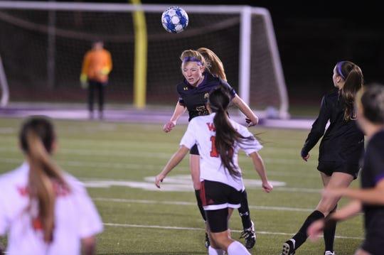 Wylie's Ella Scott (15) heads the ball against Wichita Falls High at Bulldog Stadium on Friday.