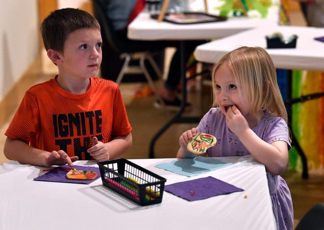 Blake Hailey and his cousin Emery, ages 6 and 5, make and eat kite-themed cookies at the Old Jail Art Center in Saturday.