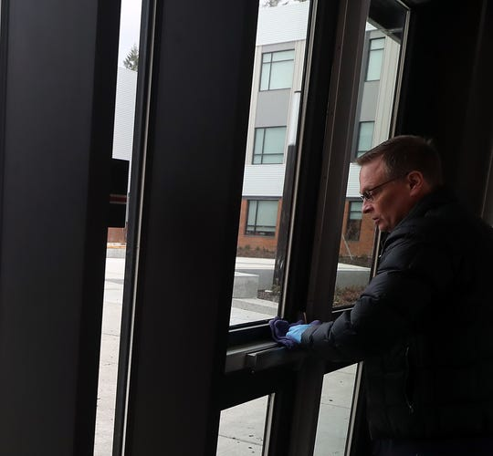 Lead custodian Michael Dyer disinfects the entry door handles to the Commons of Central Kitsap Middle School in Silverdale on Friday.