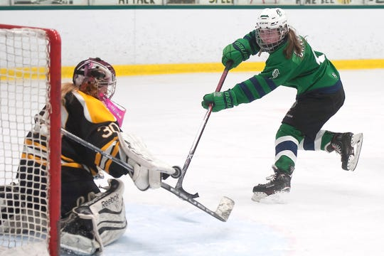 Burlington/Colchester's Madison Chagnon, right, fires a shot at Harwood goalie Kaylee Thayer during a Division I high school girls hockey semifinal at Leddy Park on Friday, March 6, 2020.