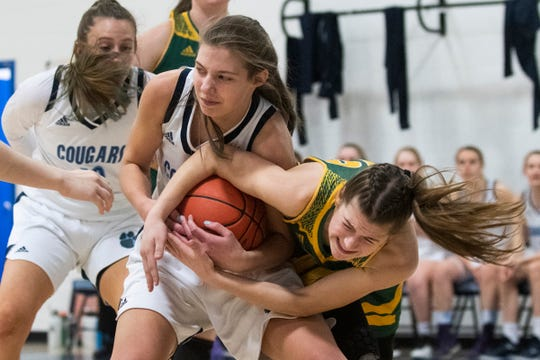 MMU's Elana Philbrick (11) and BFA's Alexis Kittell (10) battle for the ball during the girls basketball game between the BFA St. Albans Comets and the Mount Mansfield Cougars at MMU High School on Saturday March 7, 2020 in Jericho, Vermont.