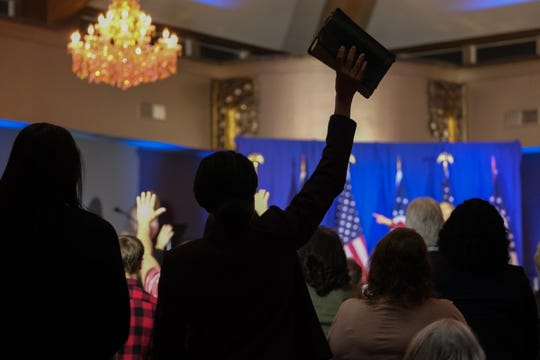 """Karla Blair holds up the Bible during the """"Evangelicals for Trump"""" event at Solid Rock Church-South in Cincinnati on Friday, March 6, 2020."""