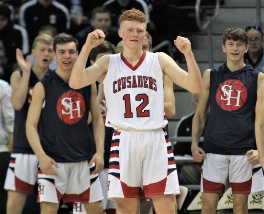 St. Henry junior Wyatt Vieth, 12, and teammates react after teammate Cody Teeten made a strong layup as St. Henry defeated Cooper 58-55 in overtime in the quarterfinals of the KHSAA Ninth Region boys basketball tournament March 7, 2020 at BB&T Arena, Highland Heights, Ky.