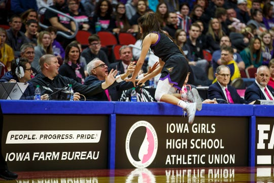 Johnston's Maya McDermott (2) jumps up onto the scorers table after chasing a ball during their 5A state championship basketball game at Wells Fargo Arena on Friday, March 6, 2020, in Des Moines.