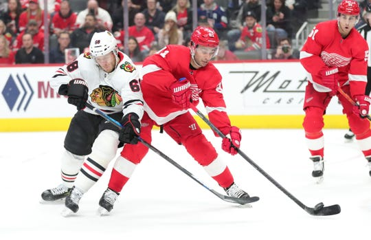 Detroit Red Wings' Frans Nielsen is checked by  Chicago Blackhawks' Slater Koekkoek in the first period Friday, March 6, 2020 at Little Caesars Arena.