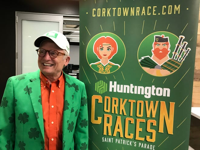 Doug Kurtis, race director for the Detroit's Corktown Races on March 15, shows off a banner -- and his emerald-green suit -- at a meeting on March 5, 2020 in Southfield of the key race volunteers, called captains.