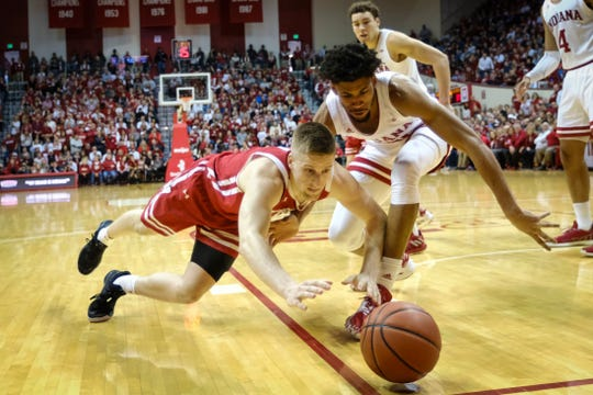 Wisconsin guard Brevin Pritzl, left, dives for a loose ball in front of Indiana forward Jerome Hunter in the second half Saturday. Wisconsin won 60-56.