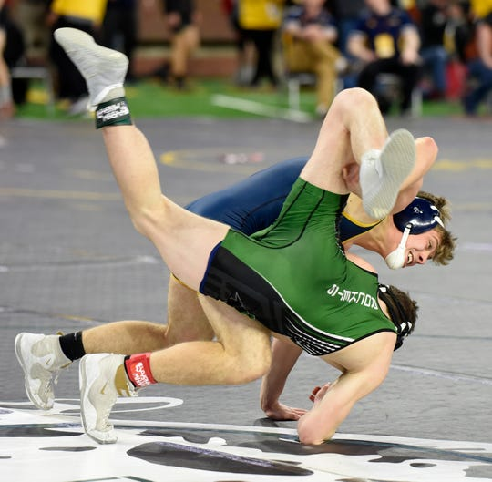 Justin Chambless, top, of Carleton Airport scores a takedown on James Rozycki of Muskegon Reeths-Puffer during their Division II 152-pound quarterfinal match at the 2020 MHSAA Individual Wrestling Tournament at Ford Field in Detroit.