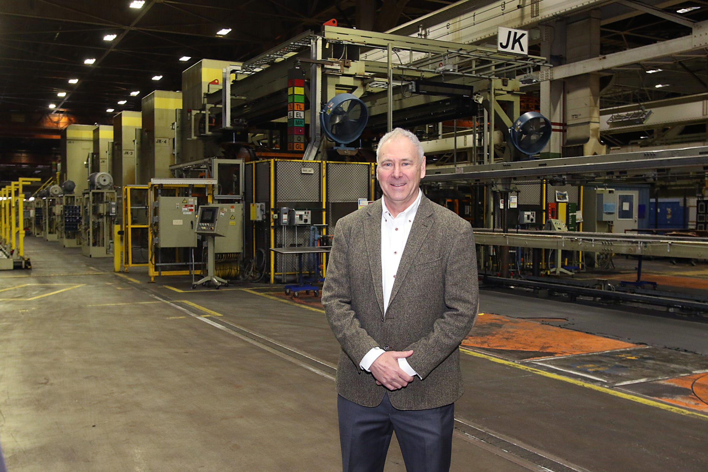 CEO Steve Burns stands In front of one of four metal stamping machines inside the Lordstown plant.