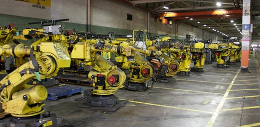 Rows and rows of robots have been removed from the assembly lines and stored inside the idle plant.