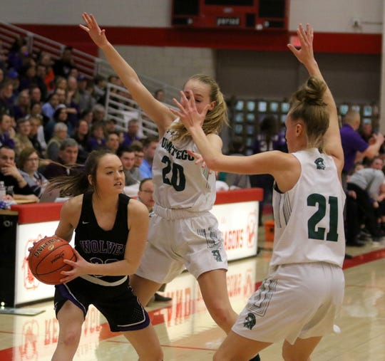 Riley Cunningham of Union Springs is defended by Unatego twins Meghan Perry (20) and Morgan Perry (21) during Unatego's 42-26 win in the Section 4 Class C girls basketball championship game March 7, 2020 at SUNY Cortland.