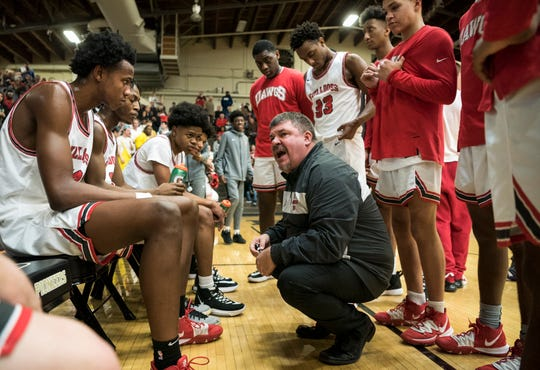 Bosse coach Shane Burkhart talks to his team during a timeout in the second quarter of the Bulldogs' loss to Heritage Hills.