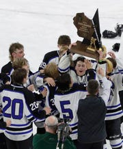 St. Mary's Springs Academy players hold up the state championship trophy after winning the WIAA Division 2 state championship game against Northland Pines on Saturday at Alliant Energy Center in Madison.