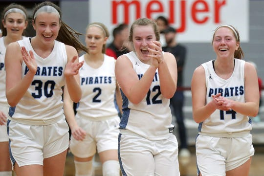 Bay Port's Mady Draak (30), Emma Krueger (12) and Alaina Abel (14) celebrate their victory over Kimberly during their WIAA Division 1 girls basketball sectional final game Saturday at Green Bay West High School.