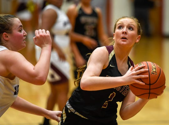 Webster County's Marissa Austin (2) looks to shoot over Madisonville's Kara Franklin (13) as the Webster County Lady Trojans play the Madisonville Lady Maroons in the Second Region semifinals at Christian County High School Friday, March 6, 2020.