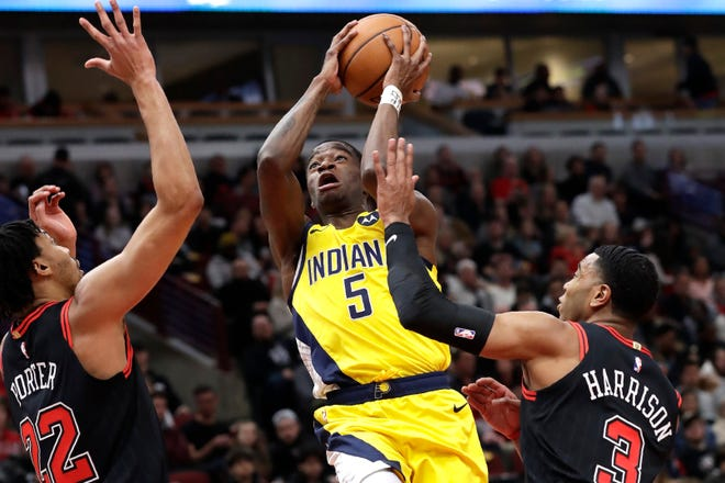 Indiana Pacers guard Edmond Sumner, center, drives to the basket against Chicago Bulls forward Otto Porter Jr., left, and guard Shaquille Harrison during the first half of an NBA basketball game in Chicago, Friday, March 6, 2020. (AP Photo/Nam Y. Huh)
