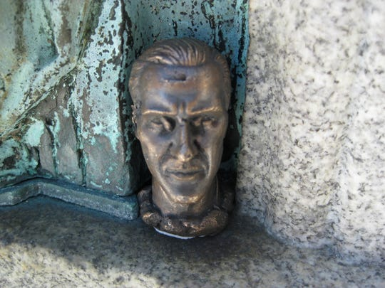 "This tiny statue, called ""The Statesman,"" was hidden on a relief at the Indiana Statehouse in 2009 by Dominic Sansone.  He hid little ""monuments,"" tiny pieces of art, in nooks and crannies around town as part of a Herron class assignment called ""Urban Art Context.""  Twenty pieces were placed, but only one remains, a tiny bronze face placed in the Artsgarden.  This one is now gone."