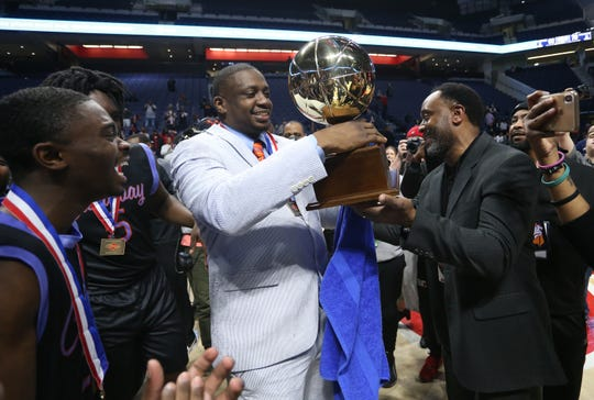 Callaway head coach David Sanders accepts the MHSAA Class 5A basketball championship trophy from Orien Watson.