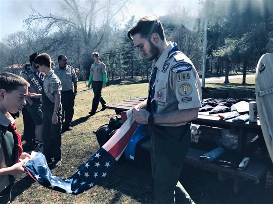 Joseph Innocenti-Travis (right) led a flag retirement ceremony Saturday at Alley Park. He and others built a fire pit at the park to retired old and worn American flags for his Eagle Scout community project.