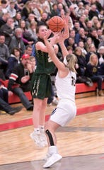 Howell's Maeve St. John, guarded by Hartland's Nikki Dompierre, makes a 3-pointer on her way to a 17-point performance in the district championship game at Holly on Friday, March 6, 2020.