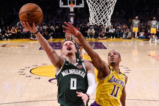 Bucks guard Donte DiVincenz shoots around Lakers guard Dion Waiters on Friday night.