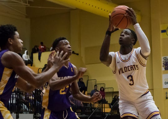 Wossman's Devonte Austin (3) drives a lane in front of a pair of St. Martinville defenders during the playoff game at Wossman High School in Monroe, La. on March 6.