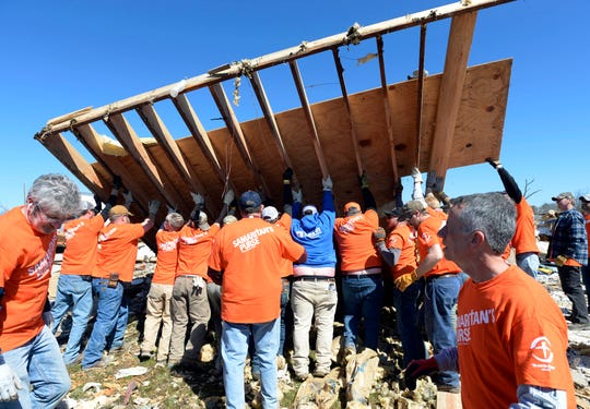 Samaritan Purse volunteers lift a side wall section of a tornado destroyed house while clearing an area around home on Saturday, March 7, 2020, in Cookeville, Tenn.