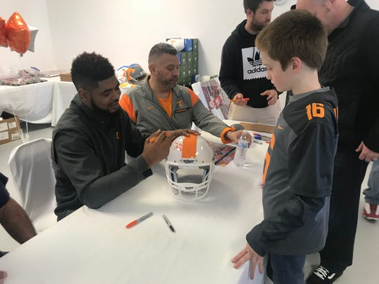 Former Vols wide receiver Jauan Jennings signs a helmet for a young fan during an autograph session at Man Cave Ink in Mt. Juliet on March 7, 2020.