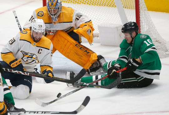 Nashville Predators defenseman Roman Josi (59) and Dallas Stars right wing Corey Perry (10) battle for the puck as Predators goaltender Juuse Saros (74) looks on during the second period of an NHL hockey game Saturday, March 7, 2020, in Dallas.