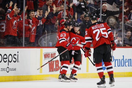 New Jersey Devils left wing Jesper Bratt (63) celebrates with teammates after scoring against St. Louis Blues goaltender Jordan Binnington during the first period of an NHL hockey game, Friday, March 6, 2020, in Newark.