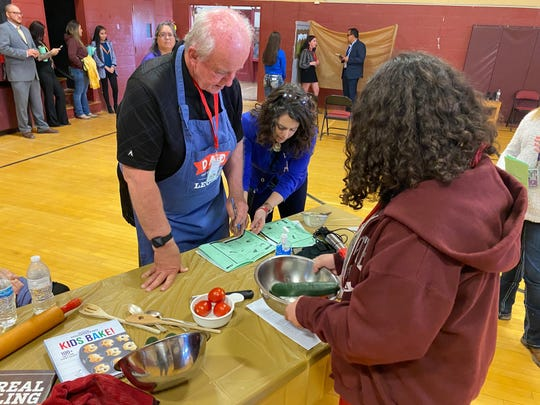 Fred Davis, left, a volunteer judge for The Amazing Shake at the Mesilla Valley Leadership Academy, grades a student participant during a mock cooking show segment.