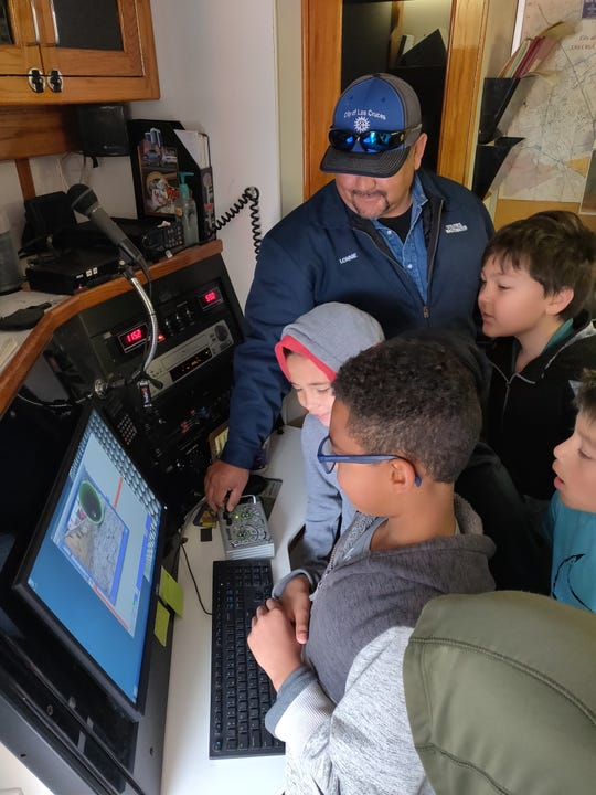Las Cruces Utilities Operator Lonnie Orona, wastewater collection inspector, shows students the image that the little truck sends back, allowing close inspection of the inside of city sewer pipes.