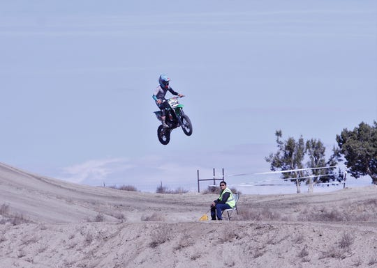 A rider goes over a jump, Saturday, March 7, 2020, while practicing at the Aztec Motocross Track.