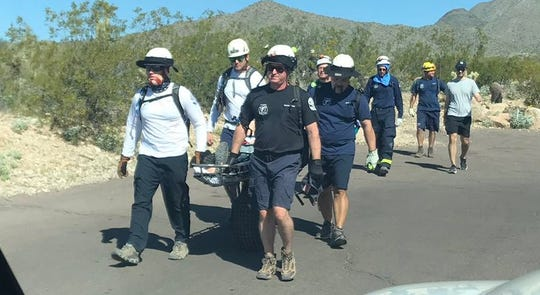 First responders carry the 77-year-old man who was bitten by a rattlesnake while hiking in Scottsdale on Saturday, March 7, 2020.