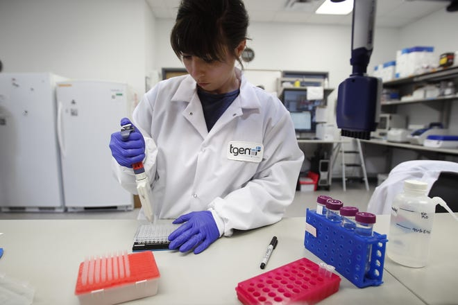 A TGen scientist prepares genetic material for testing. TGen is handling genetic material from live samples of COVID-19 and analyzing it to figure out the source of positive cases in the state.