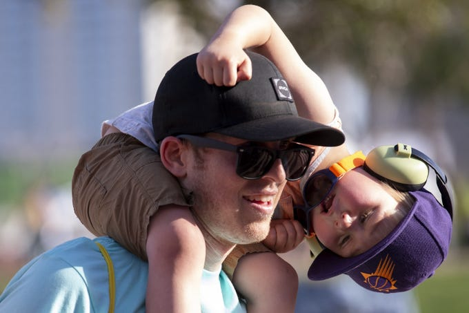 Jordan Perry carries Remy Perry, 3, while Toubab Krewe performs during McDowell Mountain Music Festival on March 6, 2020, at Margaret T. Hance Park in Phoenix.