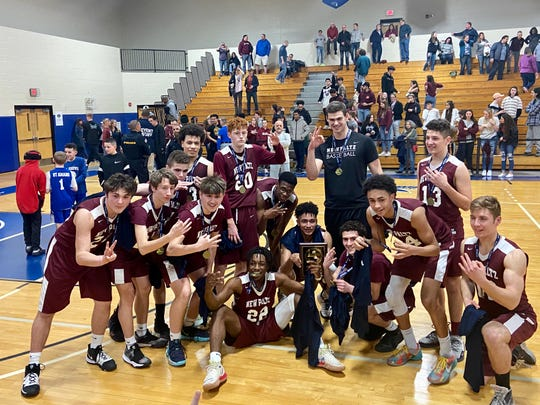 The New Paltz boys basketball team poses in celebration after beating Monticello in overtime to win a third straight Section 9 Class A title.