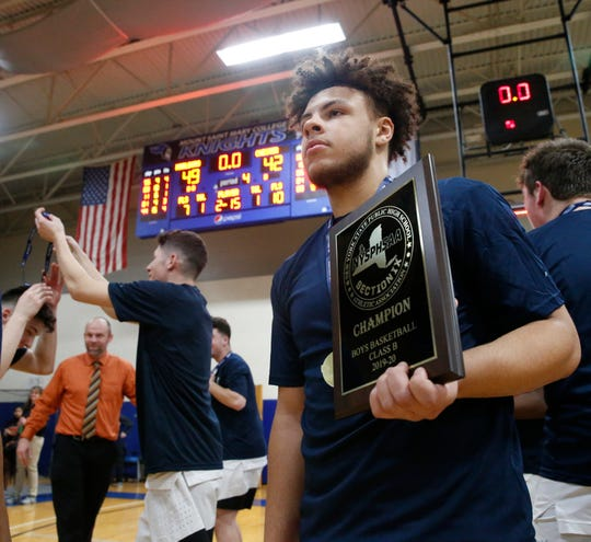 Marlboro senior CJ Faircloth clutches the Section 9 Class B championship plaque after his team defeated Chester in the final on Friday.