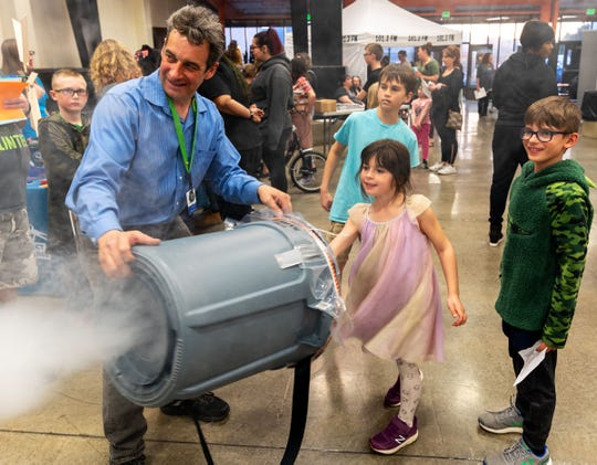 Emmeline Nomicos, 6, from Cottonwood Elementary, shoots fog with some help from Nathan Tobey at the Fernley High School STEM Festival.