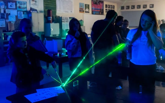 Students try to direct a laser pointer at the light show exhibit at Fernley High School's STEM Festival.