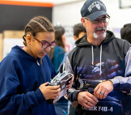 Madeline Huie, 10, flies an airplane simulator with assistance from Michael Durso, a member of the High Desert Radio Control Club, at Fernley High School's STEM Festival.